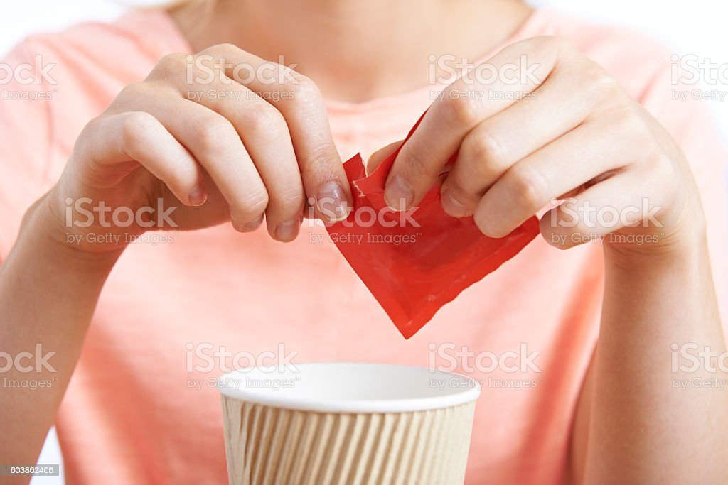 Woman Adding Artificial Sweetener To Coffee stock photo