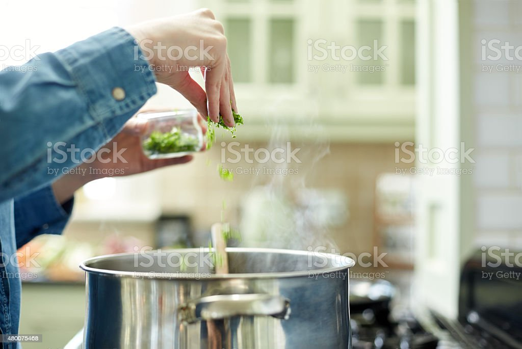 Woman adding cilantro to cooking pot stock photo