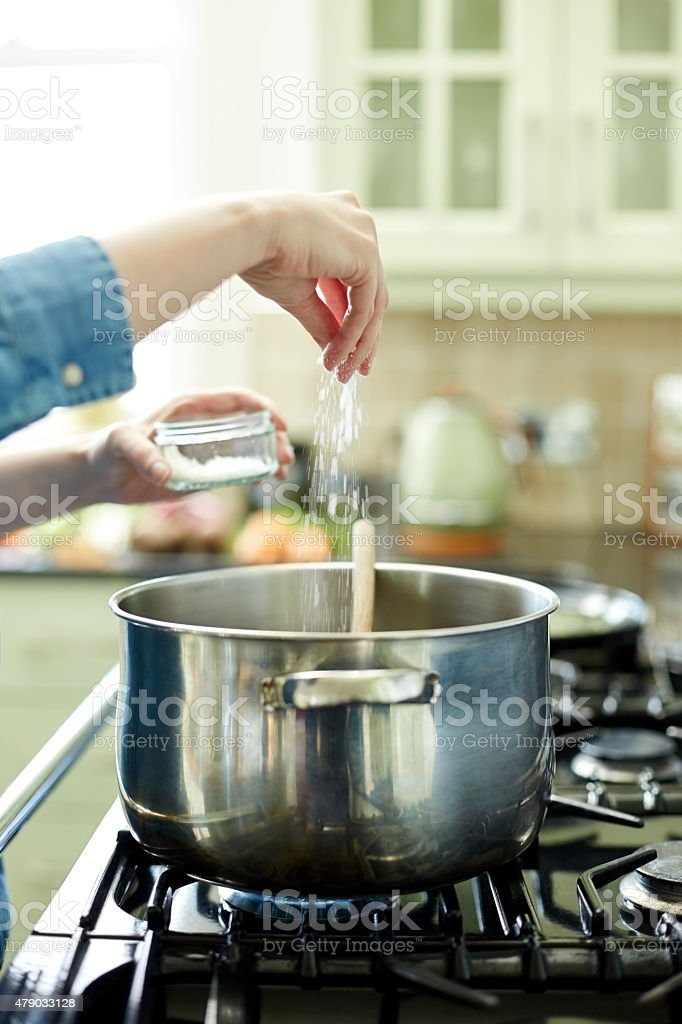 Woman adding pinch of salt in cooking pot on stove stock photo