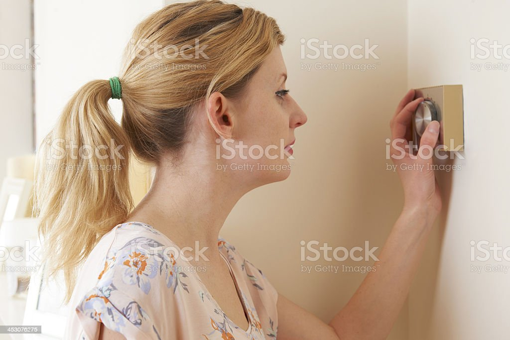 Woman Adjusting Central Heating Thermostat Control royalty-free stock photo