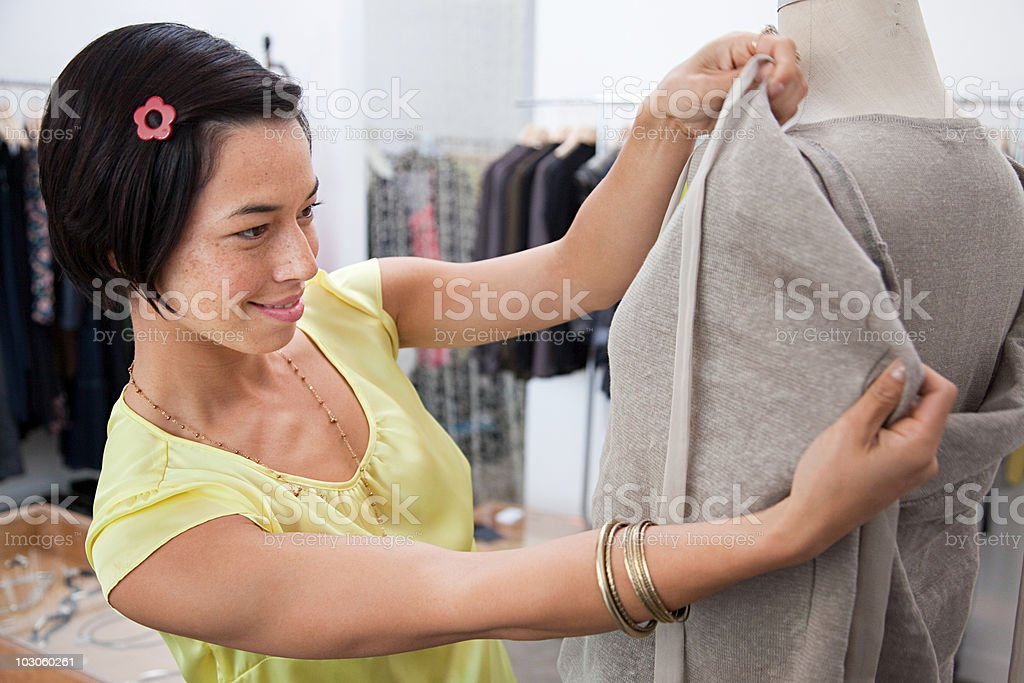 Woman adjusting clothes on mannequin stock photo