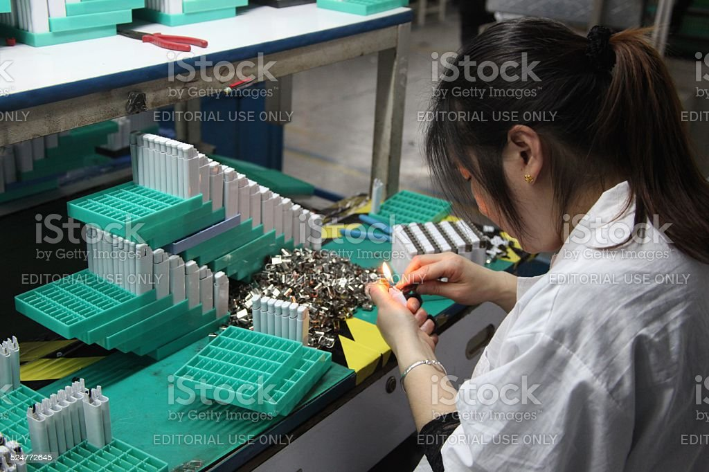Woman adjusting lighter in factory. stock photo