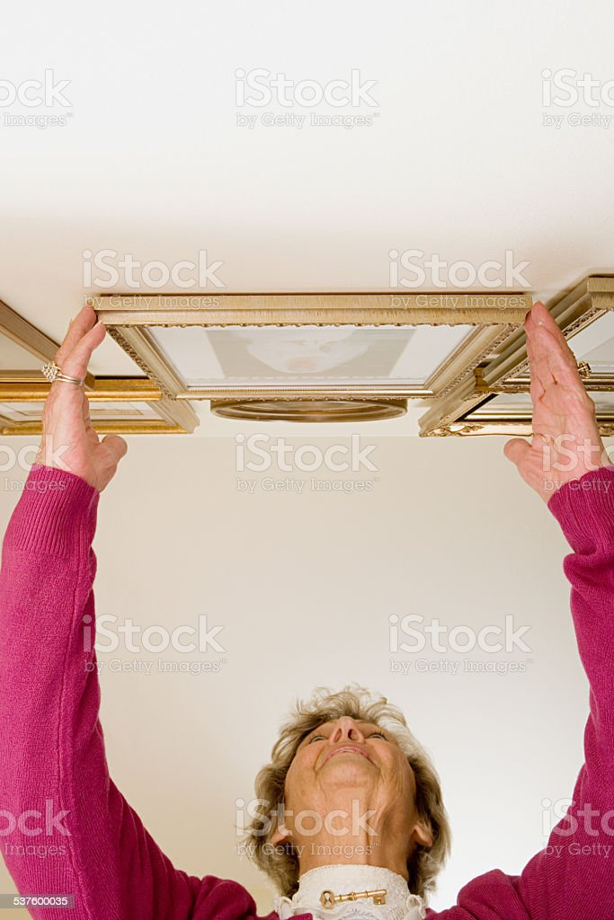 Woman adjusting picture frames stock photo