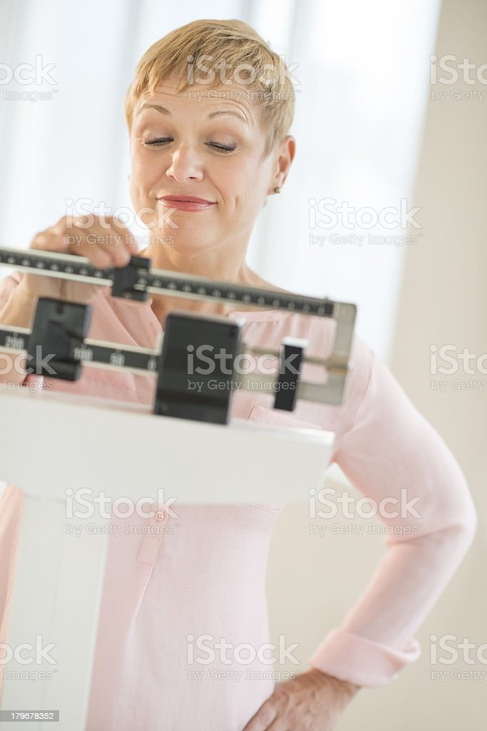 Woman Adjusting Sliding Weight Scale royalty-free stock photo