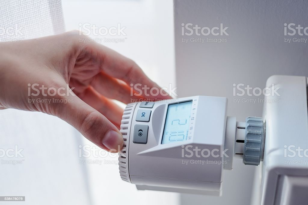Woman adjusting temperature of home heater stock photo