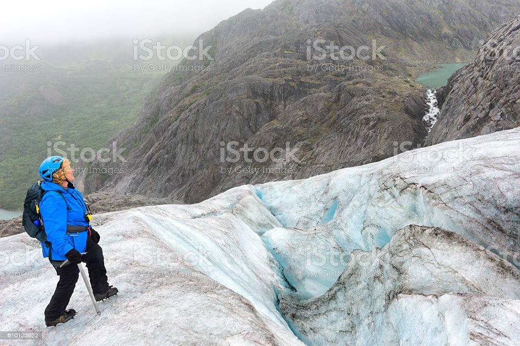 Woman admires epic glacial landscape stock photo
