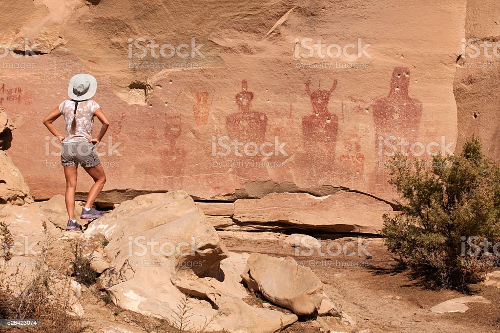 Woman admires Sego Canyon vandalized rock art panel Utah stock photo