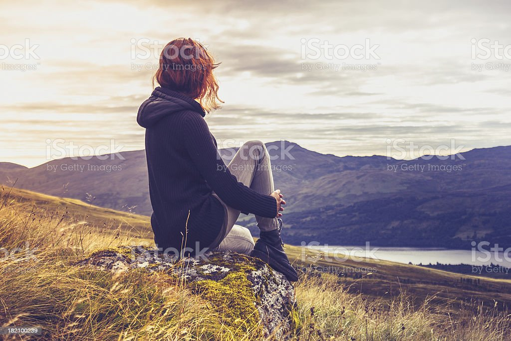 Woman admiring sunset from mountain top stock photo