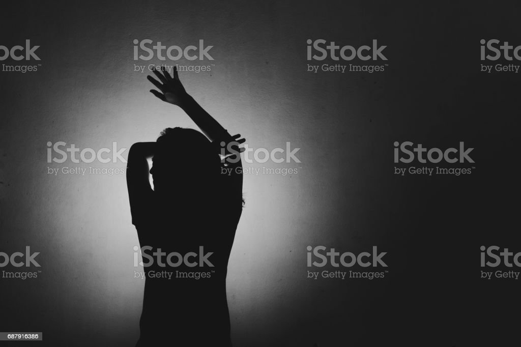 woman afraid of something, covering face and head with light behind stock photo