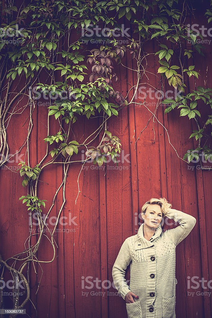 Woman against red wall with ivy stock photo