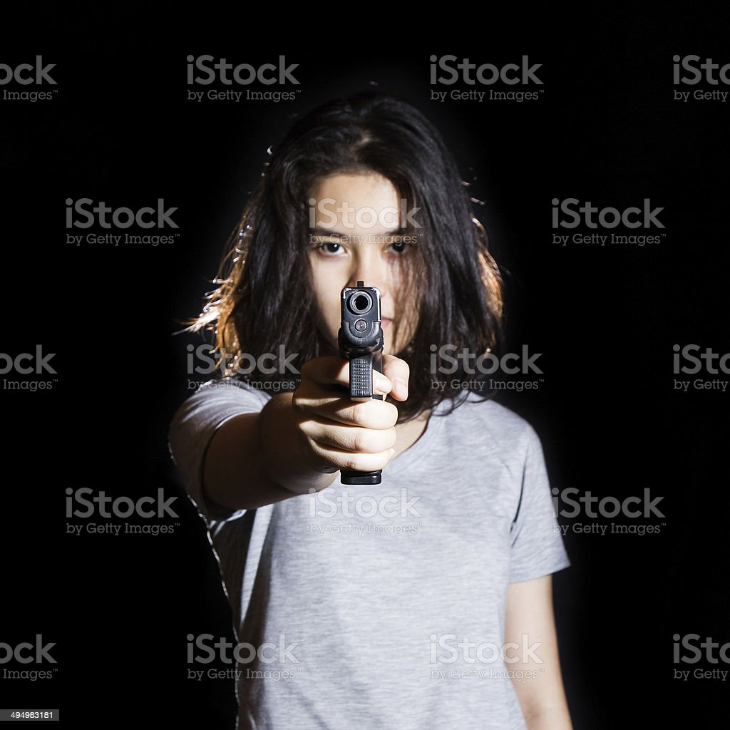 Woman aiming a gun isolated on black background. stock photo