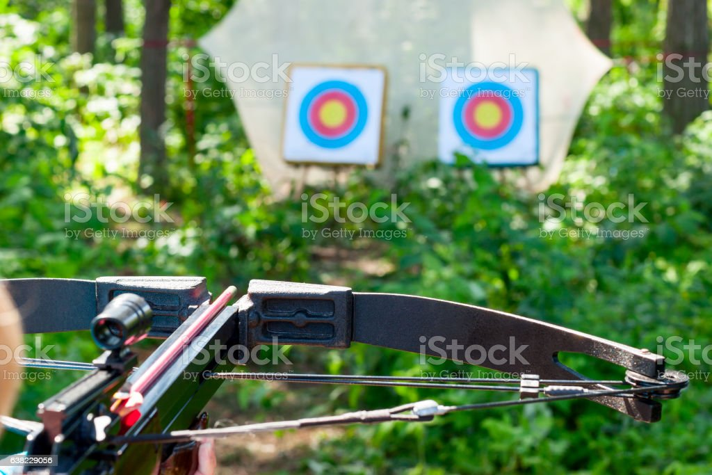 Woman aiming crossbow at target stock photo