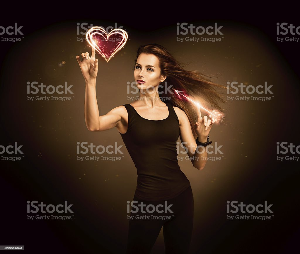 Woman Aiming to the Glowing Heart with an Arrow stock photo