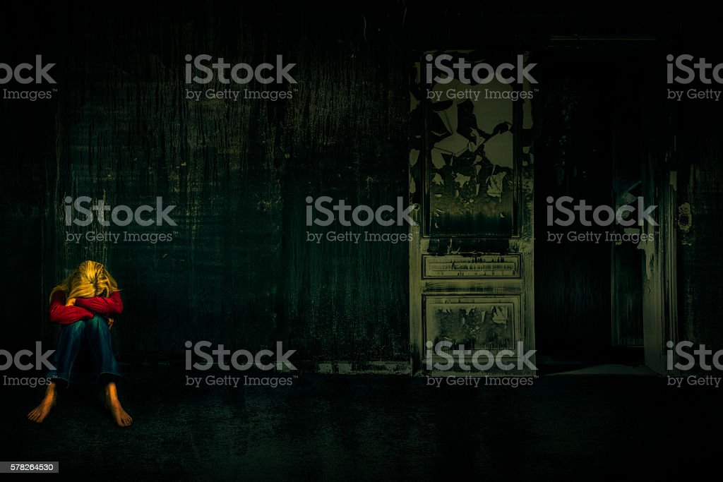 woman alone in a dark room stock photo
