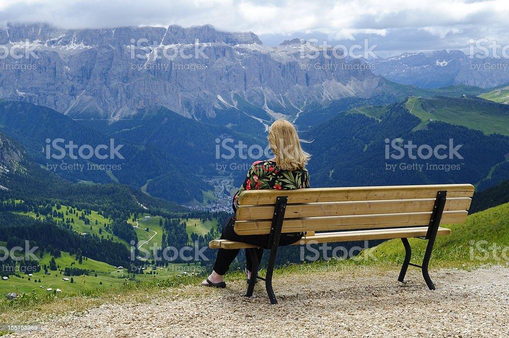 Woman alone on bench enjoying view at Val Gardena, Italy royalty-free stock photo