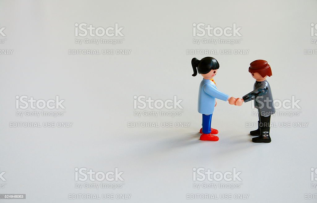 Woman and a man shaking his hands stock photo