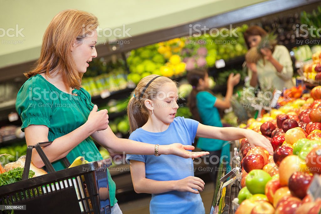 A woman and a young girl examine apples in a store royalty-free stock photo