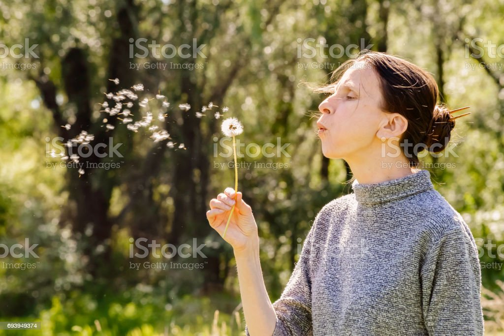 Woman and Blowball (Dandelion) stock photo