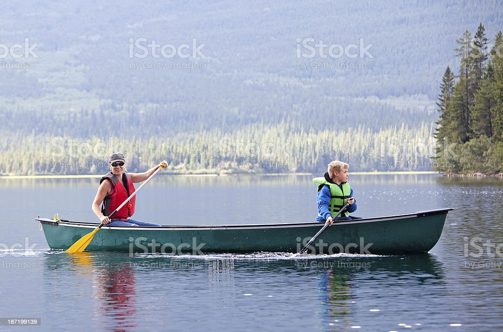Woman and Child Canoeing on Mountain Lake stock photo