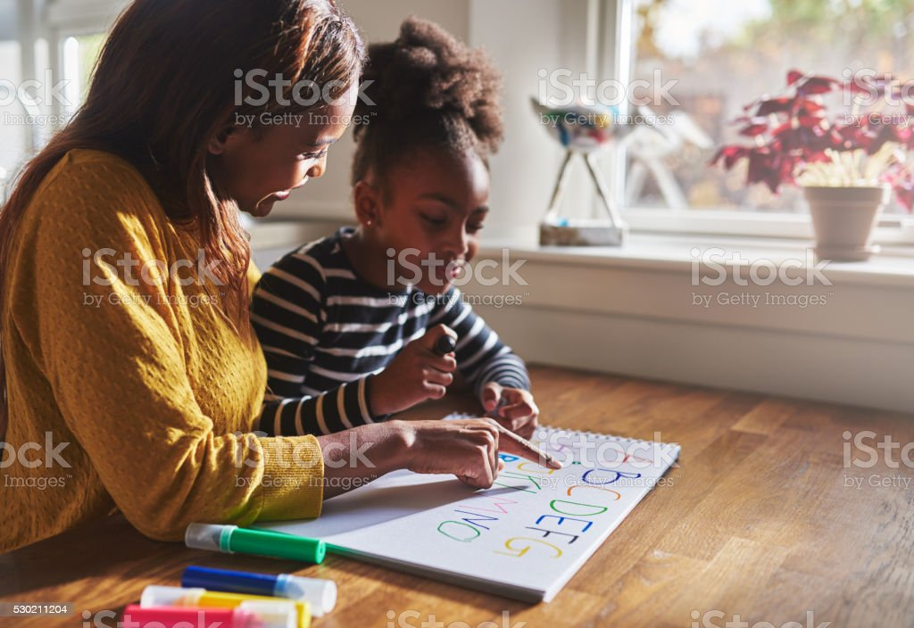 Woman and child learning alphabet stock photo