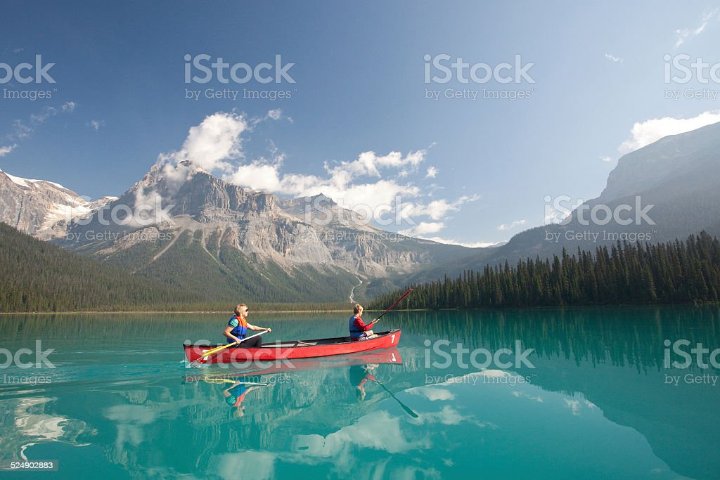 Woman and Child Paddling on Mountain Lake stock photo