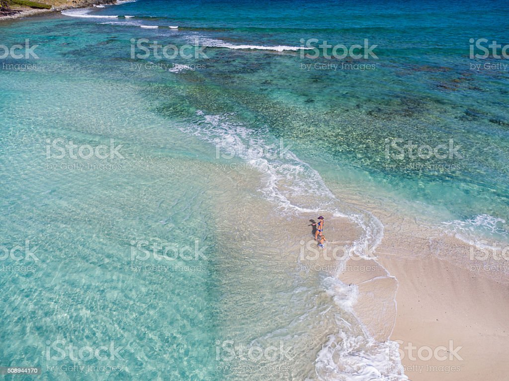 Woman and child playing on a tropical beach stock photo