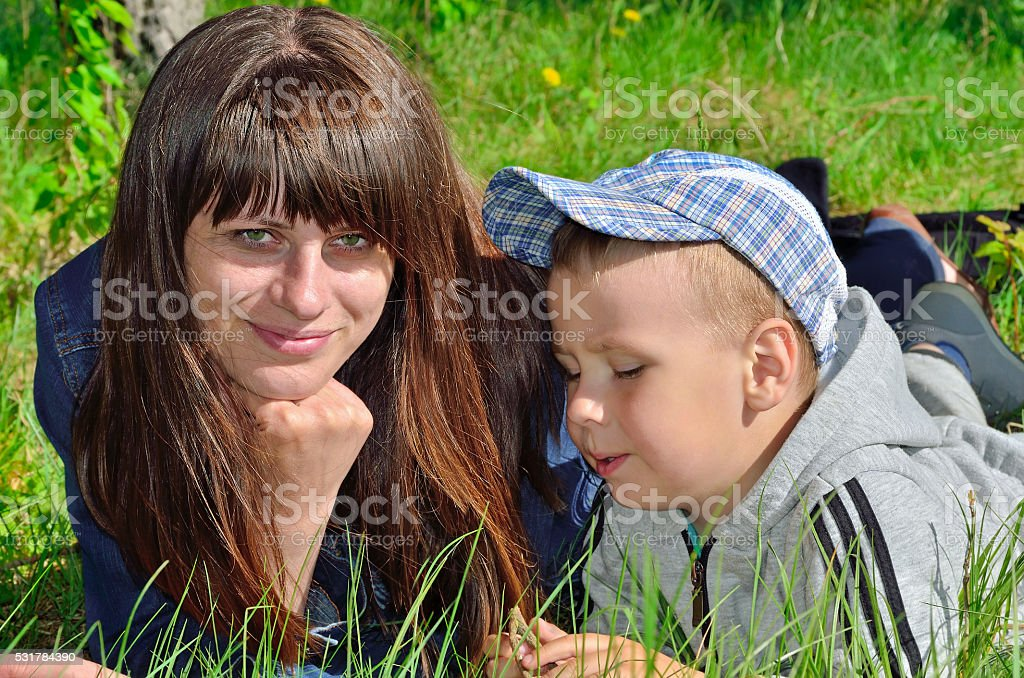 Woman and child playing on green grass stock photo
