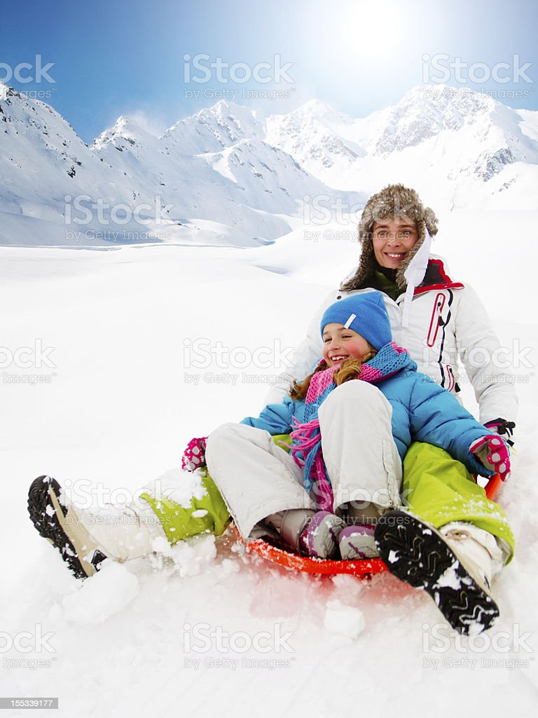 Woman and child sledding in the Italian Alps royalty-free stock photo