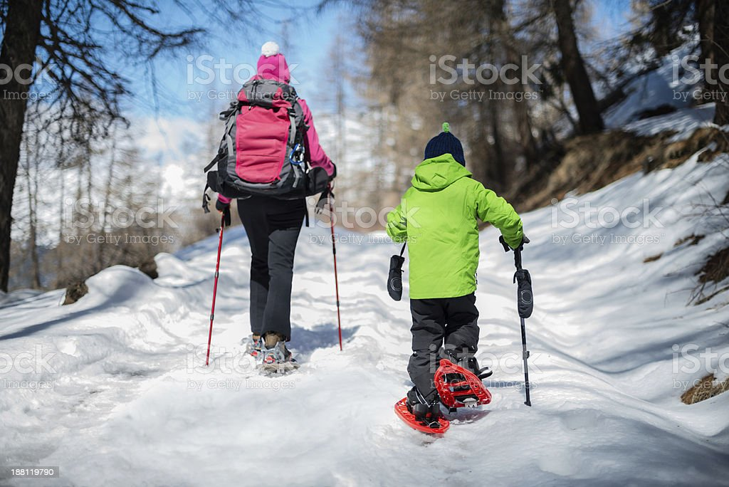 Woman and child snowshoeing outdoor stock photo