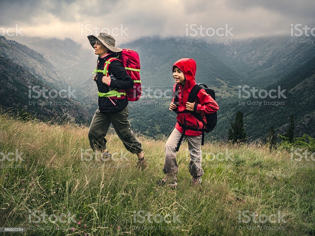 Woman and child trekking in the mountains stock photo
