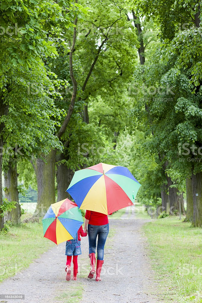 Woman and child with umbrellas in spring alley royalty-free stock photo
