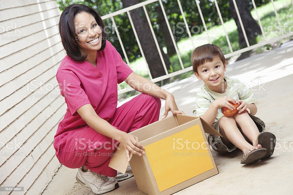 Woman and childing sitting with donations box stock photo