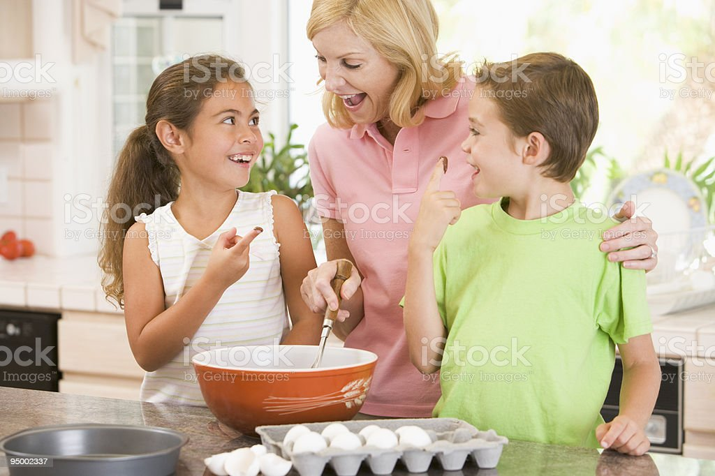 Woman and children in kitchen baking stock photo