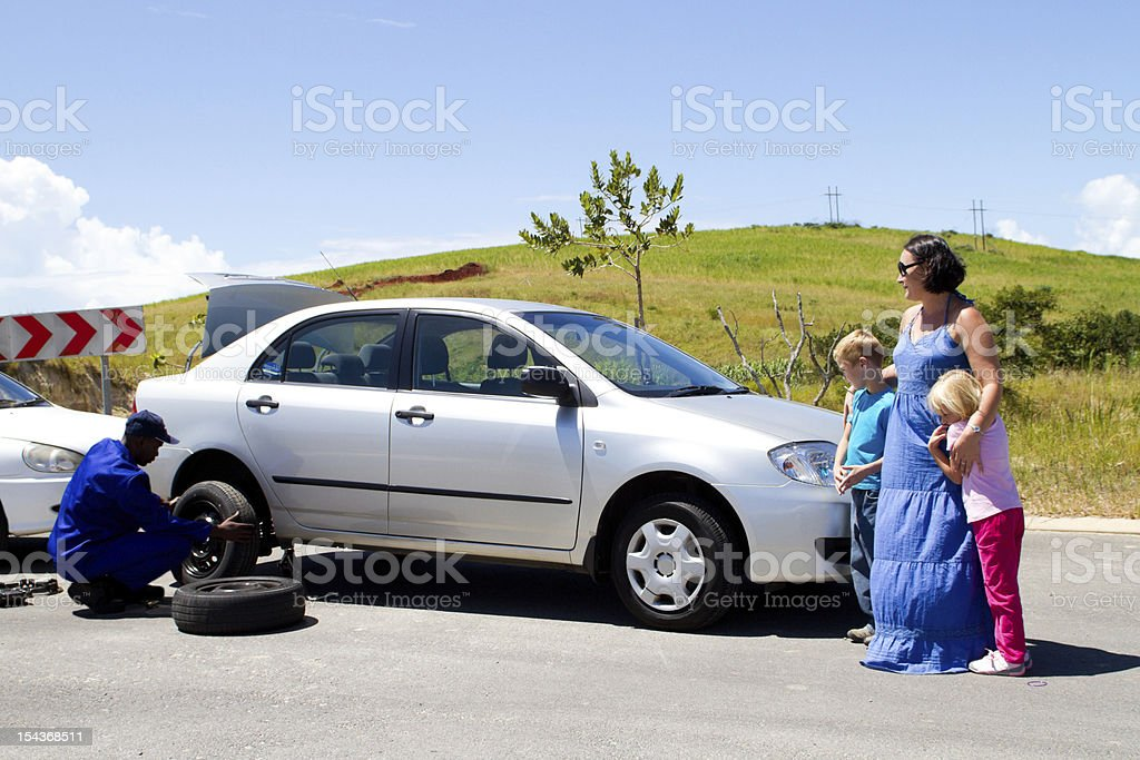 Woman and children watch as man changes their car tire stock photo