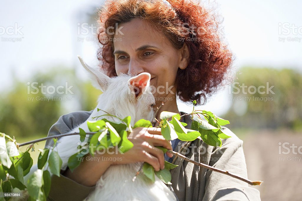 Woman and cute baby goat stock photo