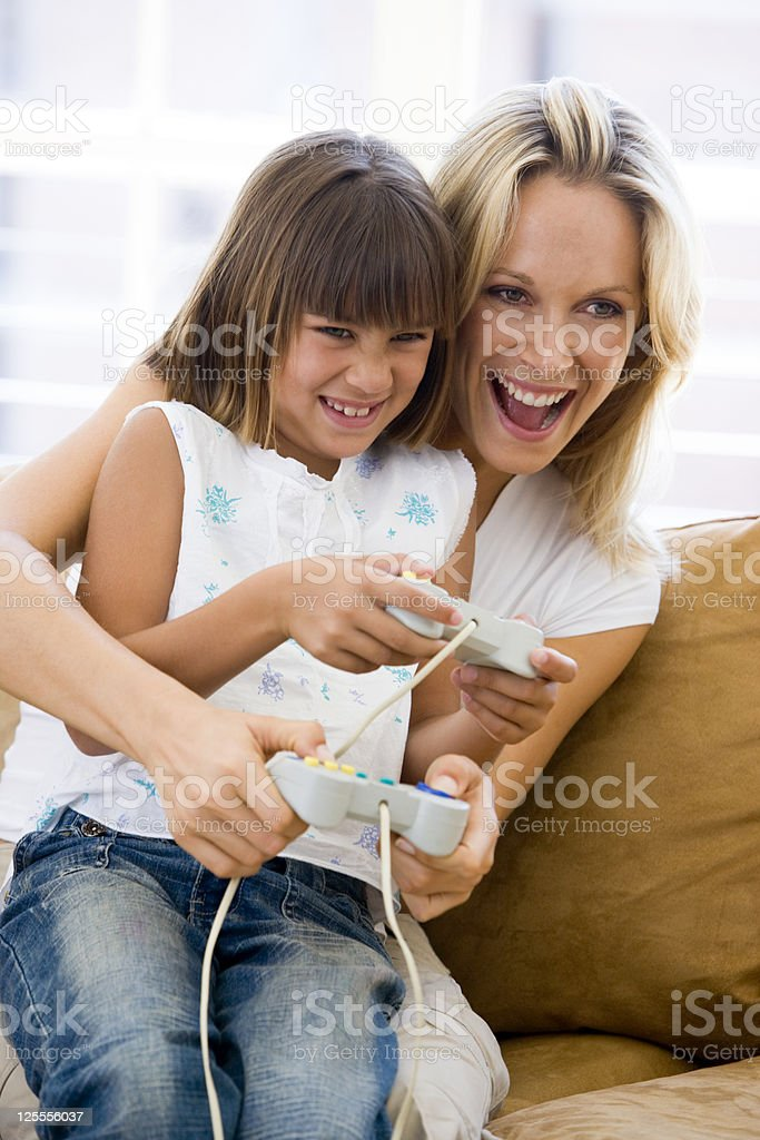 Woman and daughter in living room with video game controllers royalty-free stock photo