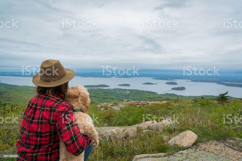 Woman and Dog Enjoy Beautiful View stock photo