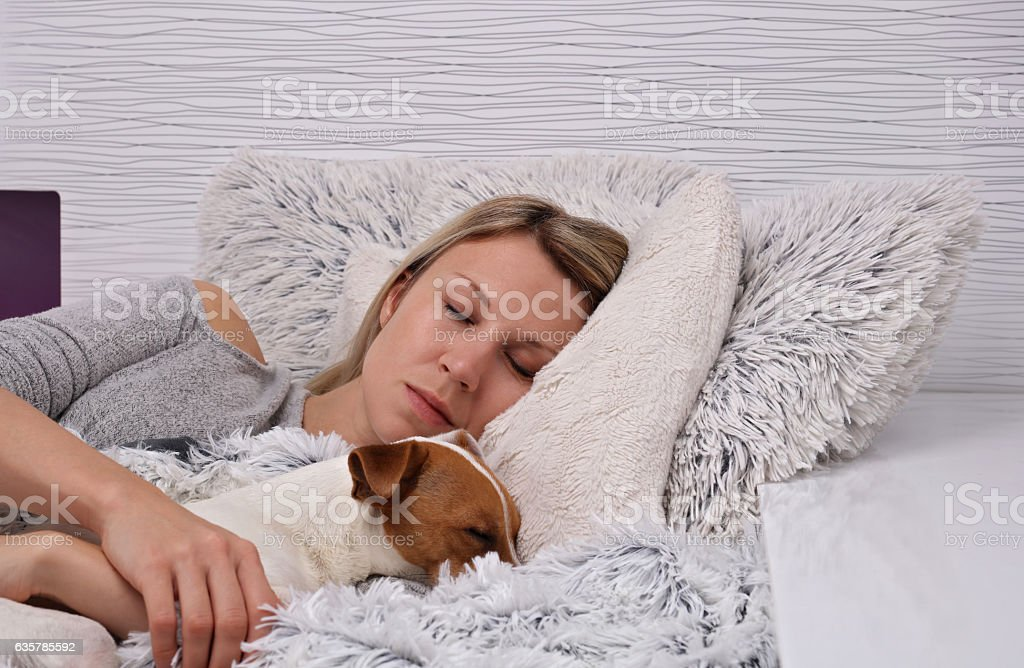 Woman and dog sleeping together. Pet Allergies concept stock photo