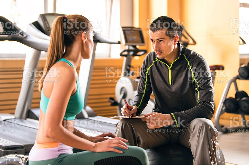 Woman and fitness instructor talking in gym stock photo