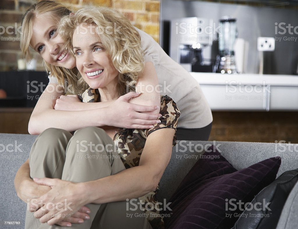 Woman and girl embracing in living room royalty-free stock photo