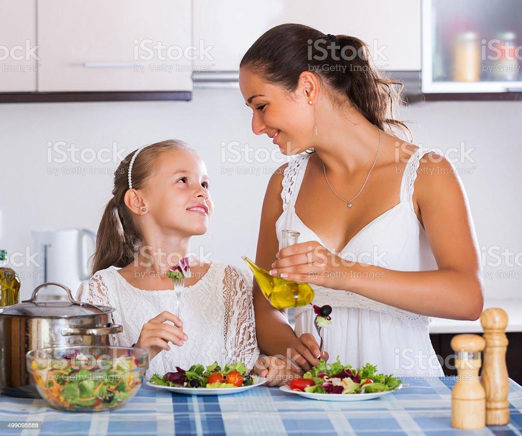 Woman and girl holding salad stock photo