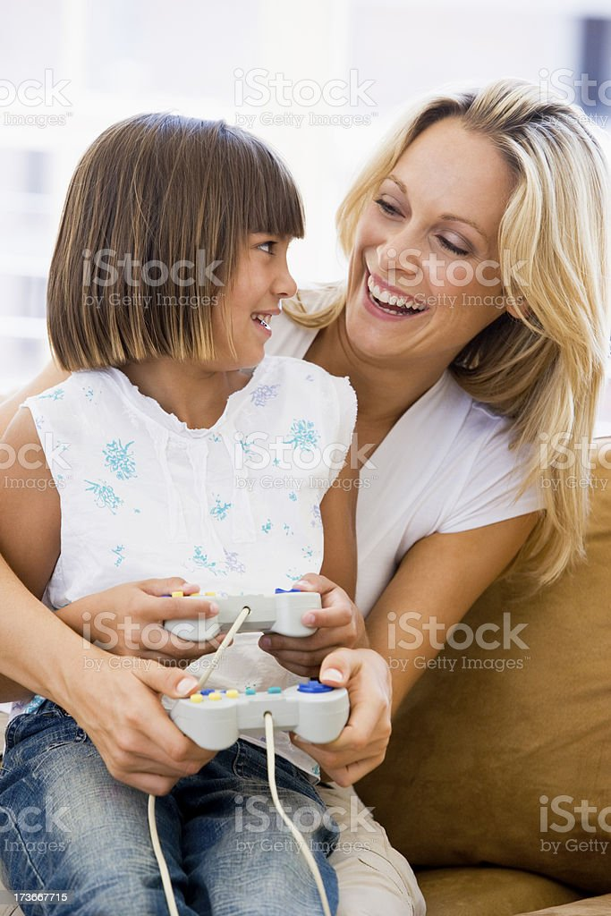 Woman and girl in living room with video game controllers royalty-free stock photo