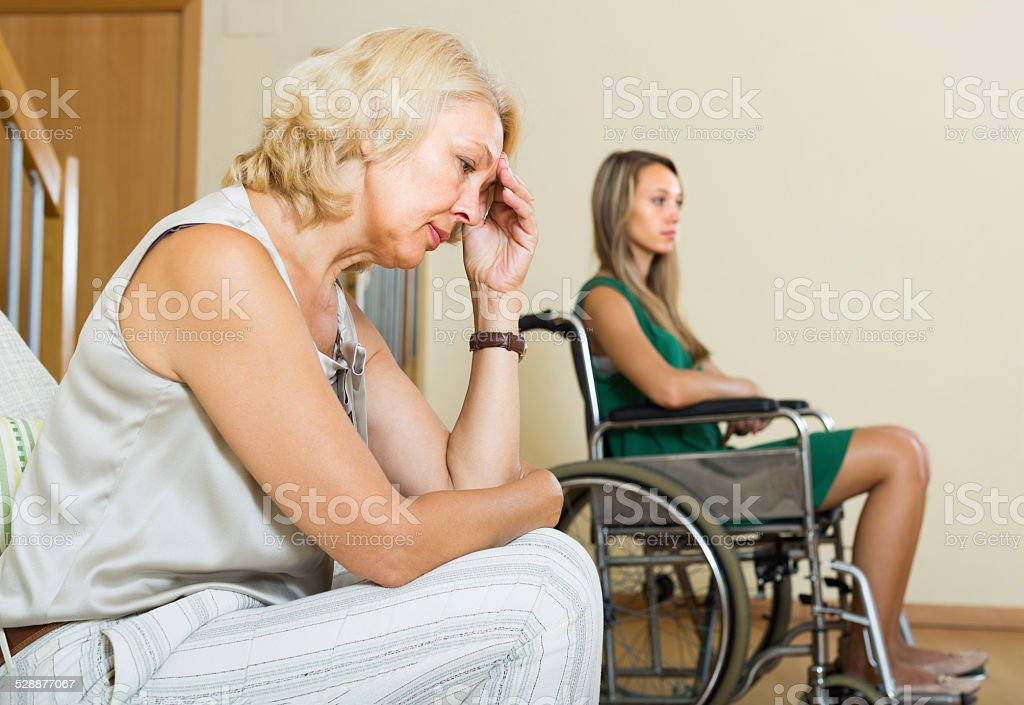Woman and handicapped female having quarrel stock photo