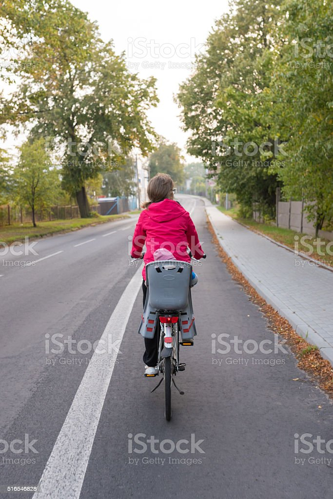 Woman and her baby traveling by bicycle stock photo
