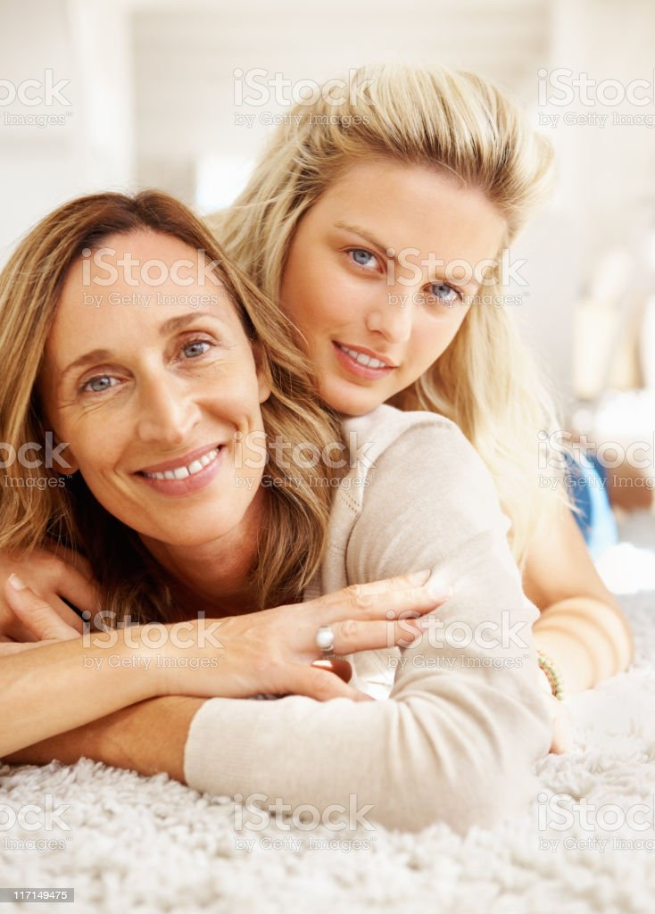 Woman and her daughter lying on a carpet royalty-free stock photo