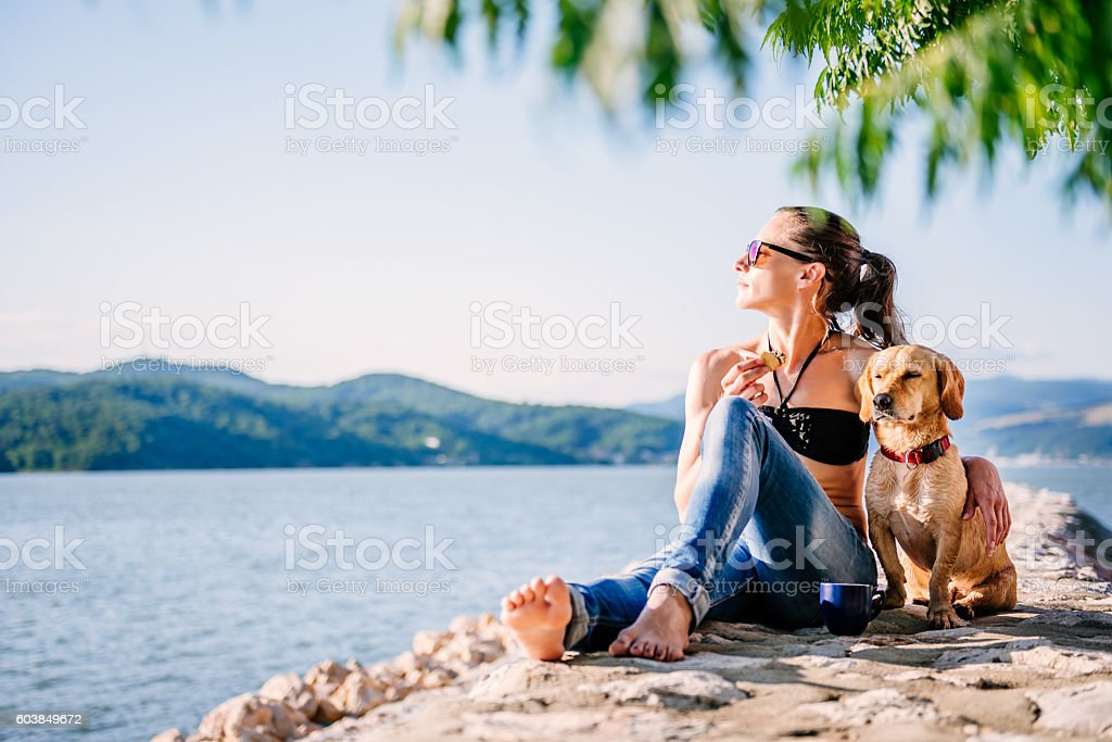Woman and her dog enjoying on a sun together stock photo
