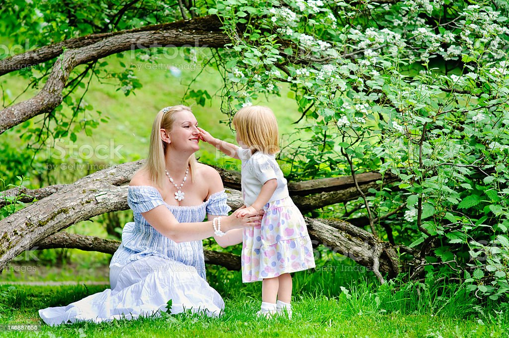 woman and her toddler daughter in a beautiful blooming garden royalty-free stock photo