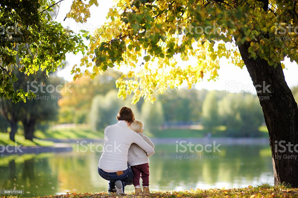 Woman and her toddler son in park stock photo