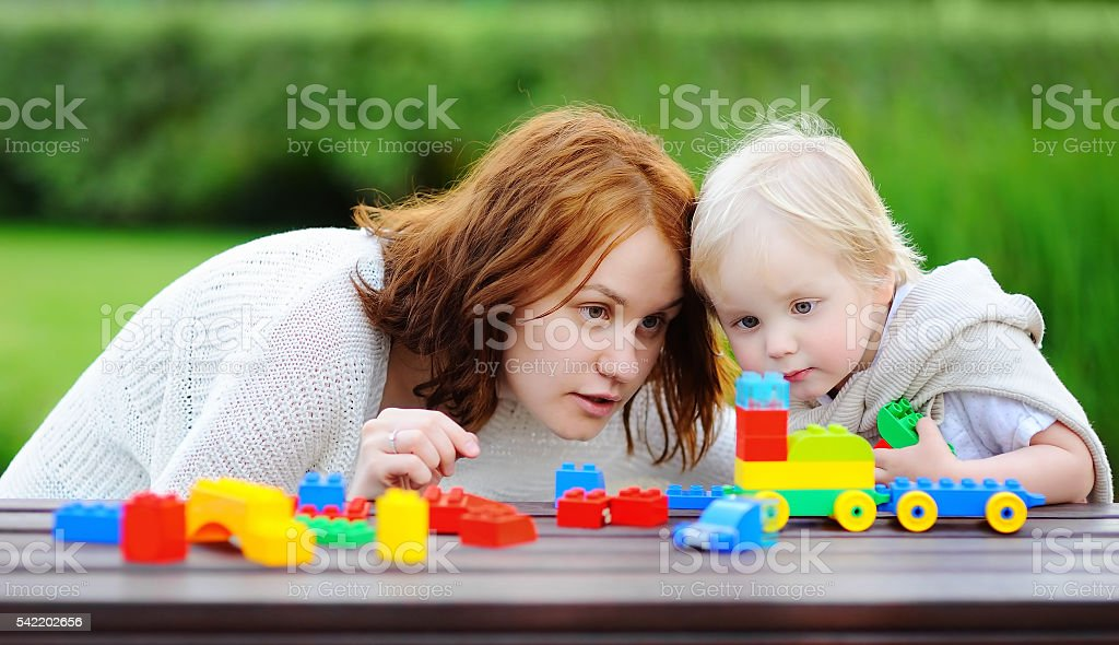 Woman and his son playing with colorful plastic blocks stock photo