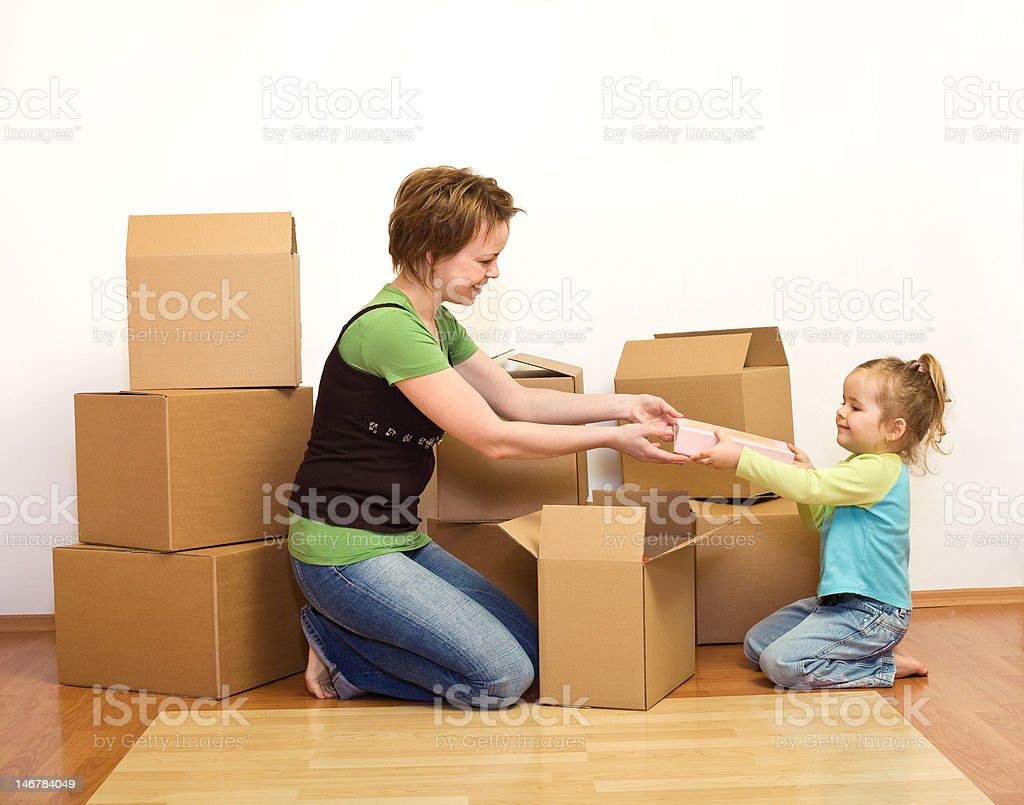 Woman and little girl in a new home unpacking royalty-free stock photo